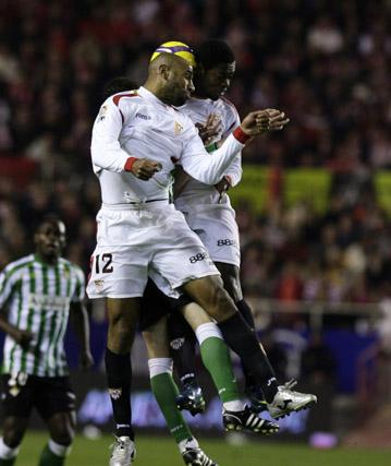 Un jugador bético entre los sevillistas Kanoute y Romaric. Emana, al fondo.  Foto: Antonio Pizarro