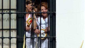 Enfermeras de la clínica Gálvez contemplan el paso de la Pollínica en el domingo de Ramos.   Foto: Sergio Camacho