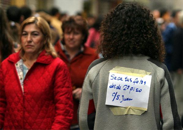 Una joven lleva a la espalda un cartel en el que ofrece su piso de calle San Juan para tomar las mejores fotografías.   Foto: Sergio Camacho