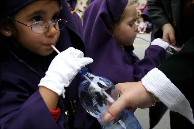 Una pequeña nazarena de la cofradía Nueva Esperanza toma agua
