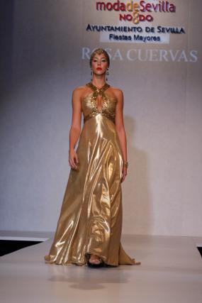 Rosa Cuervas presenta 'Mata Hari', una creación con bustos y talles realzados y construidos con drapeados junto a pedrería y vuelos asimétricos. La diseñadora combina los tonos en oro y bronce con las texturas lamés y pailletes, tejidos con efecto metalizado.   Foto: Martin Okuemotto