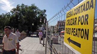Cartel que indica en el Puente de Triana la limitación de las aceras por las obras.  Foto: B.Vargas