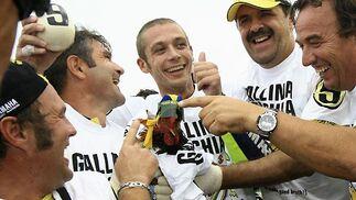"""Valentino Rossi (Yamaha) celebra el título con sus seguidores, que llevaban también camisetas con la leyenda """"Gallina vieja hace buen caldo"""" y una gallina viva.  Foto: Afp Photo / Efe / Reuters"""