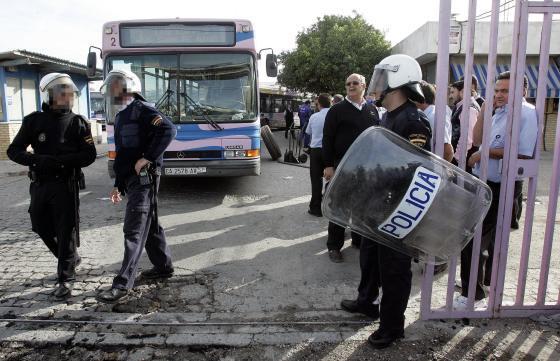 Policías con material antidisturbios controlan la salida de los garajes de Cojetusa ayer mientras reparan un autobús saboteado.  Foto: Miguel Angel Gonzalez
