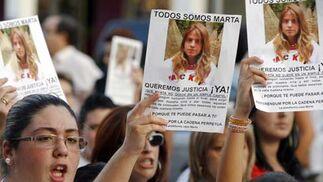 Varios manifestantes muestran la foto de la joven sevilla.  Foto: Antonio Pizarro / EFE