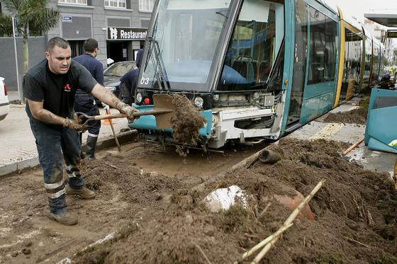 Bomberos retiran el barro acumulado en las vías del tranvía tras las fuertes lluvias caídas en Tenerife.   Foto: Cristóbal García (Efe)