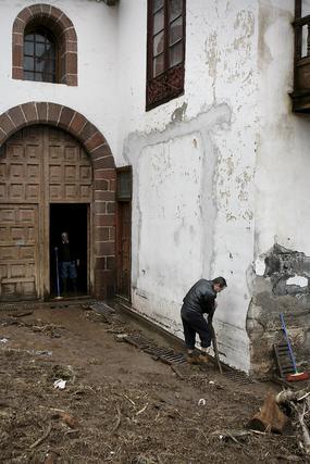 Un hombre desatasca las alcantarillas de la iglesia de La Concepción de Santa Cruz, inundada tras desbordarse el barranco de Santos por las intensas lluvias caídas en Tenerife.  Foto: Cristóbal García (Efe)