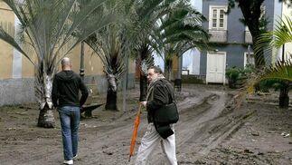 El director artístico del carnaval de Santa Cruz de Tenerife, Sergio García, camina por una calle llena de barro tras las fuertes lluvias caídas.  Foto: Cristóbal García (Efe)