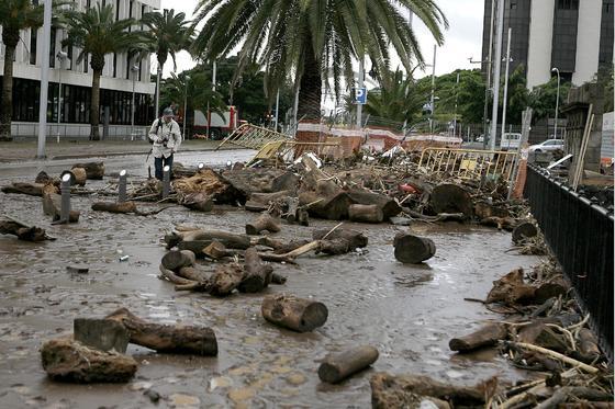 Un hombre pasa entre los restos vertidos por el barranco de Santos al desbordarse por las intensas lluvias caídas en Tenerife.  Foto: Cristóbal García (Efe)