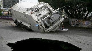 Un camión de recogida de basura atrapado en uno de los boquetes ocasionados por las fuertes lluvias caídas en Tenerife.   Foto: Cristóbal García (Efe)