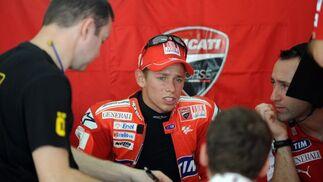 El piloto de Ducati, Casey Stoner, conversa con sus técnicos en el box durante la sesión de entrenamientos.  Foto: Agencias