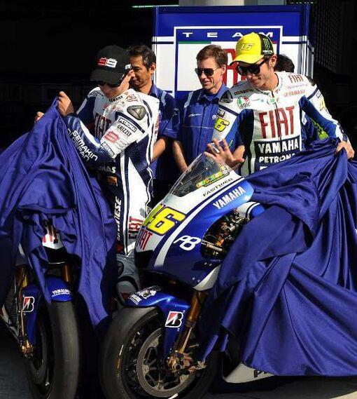 El piloto italiano Valentino Rossi (d) y el español Jorge Lorenzo (i) descubren sus nuevas motos Fiat Yamaha para la temporada 2010, sendas YZR M1.  Foto: Agencias