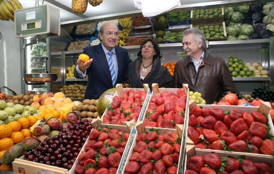El alcalde coge una naranja en un puesto de fruta.  Foto: Espínola