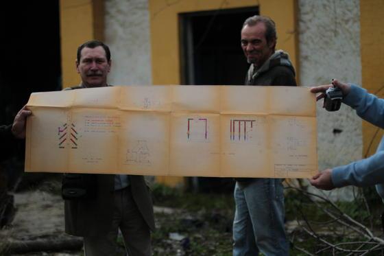 Basilio Moreno y otros activistas de la Asociación Histórica del Retiro Obrero enseñan un gran plano encontrado en el interior de la Fábrica de Vidrios.  Foto: Samara Calero