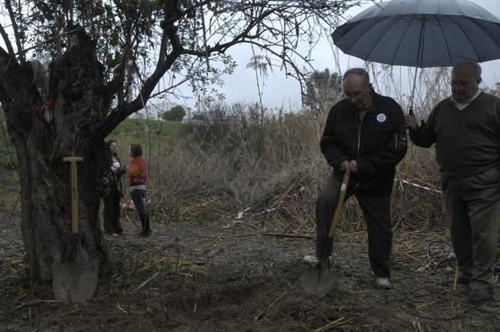 Un hombre protege de la lluvia a José Antonio Casanueva mientras cava.  Foto: Manuel Gómez
