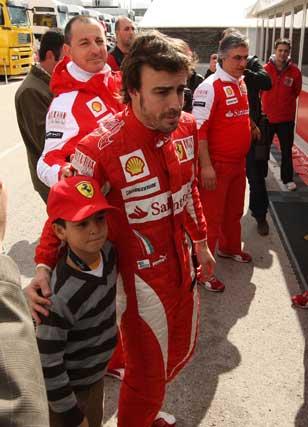 Fernando Alonso se fotografía con un joven aficionado  Foto: Juan Carlos Toro