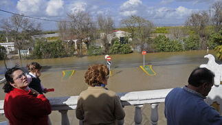 vecinos de la Algaba observan como el agua cubre la carretera.  Foto: Juan Carlos Vázquez