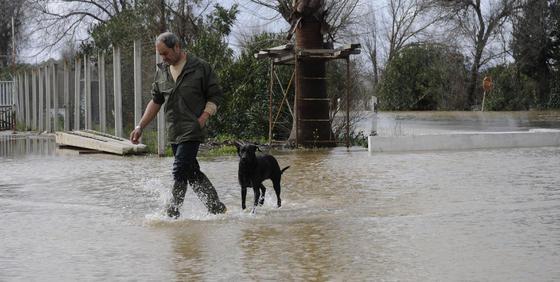 Un hombre pasea con un perro por una zona totalmente cubierta de agua.  Foto: Juan Carlos Vázquez