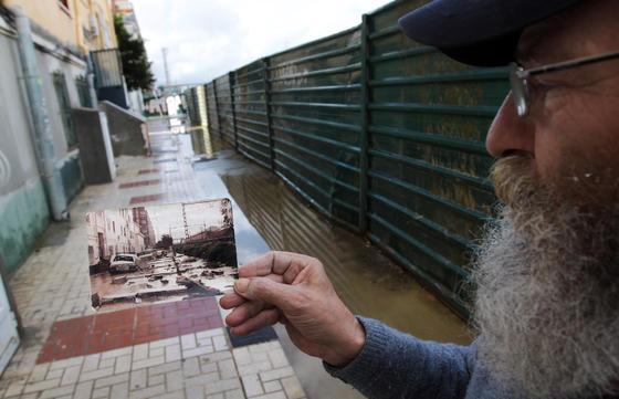 Un vecino muestra una foto de la inundación de 1989.  Foto: Migue Fernández, Sergio Camacho, Agencias