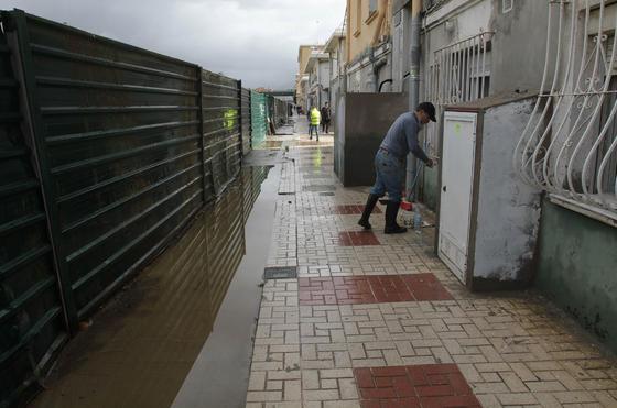 Vecinos achicando agua en la barriada de Dos Hermanas.  Foto: Migue Fernández, Sergio Camacho, Agencias
