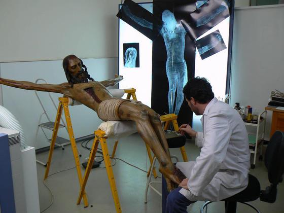Un restaurador del taller de escultura trabaja sobre la talla del Crucificado de Bornos, en Cádiz, con varias radiografías al fondo.  Foto: Ruesga Bono
