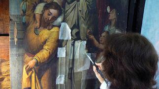 Una restauradora del IAPH trabaja sobre una tabla del retablo de la Parroquia de Santa Ana.  Foto: Ruesga Bono