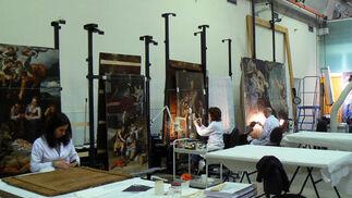 Varios trabajadores del taller de pintura del IAPH restauran las tablas del retablo de la Parroquia de Santa Ana de Pedro de Campaña.  Foto: Ruesga Bono