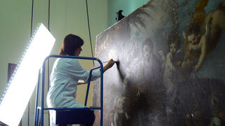 Una restauradora trabaja sobre una tabla subida en una escalera del taller.  Foto: Ruesga Bono