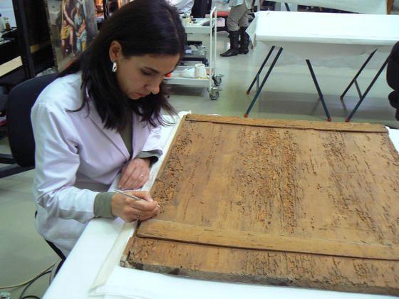Una restauradora trabaja sobre la parte trasera de una tabla en el taller de pintura.  Foto: Ruesga Bono