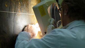 Una trabajadora del taller de pintura se ayuda de la luz para trabajar sobre una zona de la tabla.  Foto: Ruesga Bono
