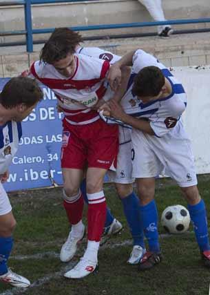 Un jugador del Granada forcejea con tres rivales  Foto: Pascu Méndez (LOF)