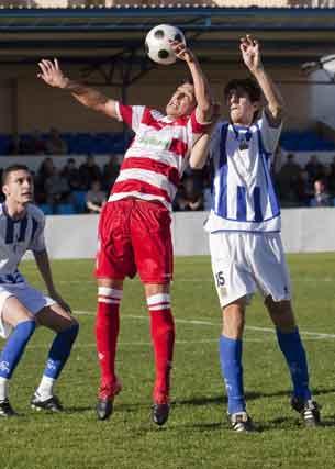 Un jugador granadino trata de cabecear un balón ante la presión de dos rivales.  Foto: Pascu Méndez (LOF)