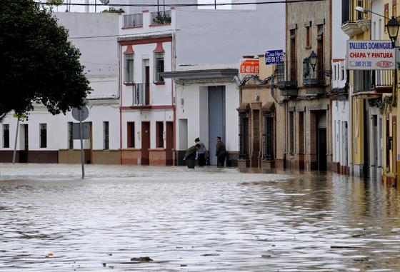 Una calle de Lora del Río inundada; al fondo, tres vecinos cubiertos de agua hasta las rodillas.  Foto: Juan Carlos Vázquez