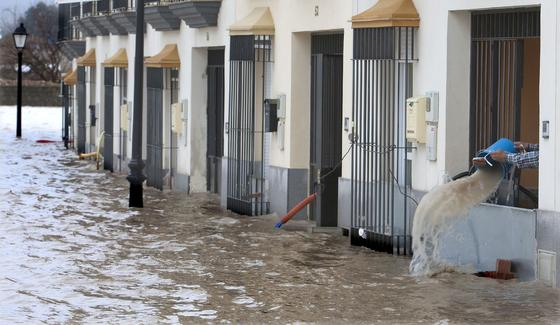 Una calle de Lora del Río inundada, y un vecino achicando agua con un cubo.  Foto: Agencias