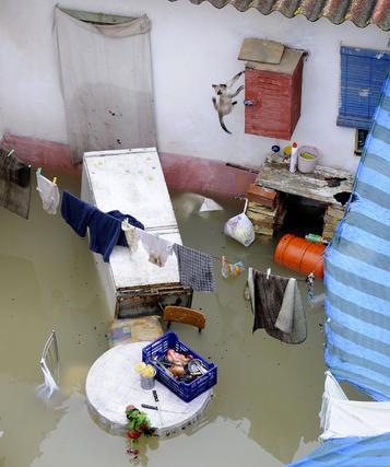 Un patio de Tocina totalmente inundado; el agua cubre los muebles y ha tirado enseres y electrodomésticos.   Foto: Juan Carlos Vázquez