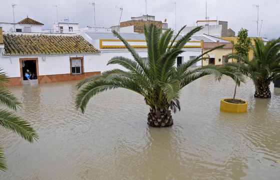 Una calle de Tocina inundada; al fondo, una mujer achicando agua.  Foto: Juan Carlos Vázquez