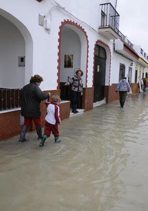 Una mujer anda con un niño de la mano por una calle de Tocina cubierta por el agua.  Foto: Juan Carlos Vázquez