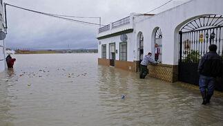 Varios vecinos de Tocina rodeados por objetos que flotan en el agua.  Foto: Juan Carlos Vázquez