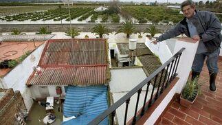 Un hombre señala desde lo alto un patio inundado en Tocina; al fondo, un campo inundado.  Foto: Agencias