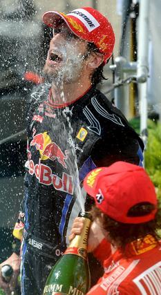 Alonso baña en champagne a Webber. / EFE