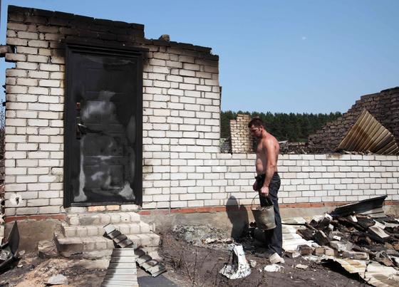 Un hombre mira su casa arrasada por las llamas. / AFP