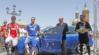 Los jugadores posan con la camiseta de la 'Champions' junto al vehículo oficial del Sevilla Fútbol Club.  Foto: Antonio Pizarro