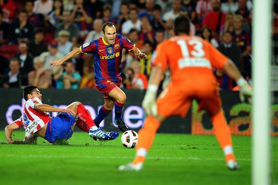 Iniesta encara al portero del Sporting tras evitar a un defensa. / AFP