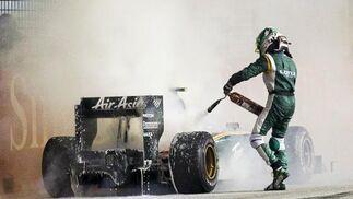 Kovalainen apaga el motor de su Lotus tras incendiarse. / EFE