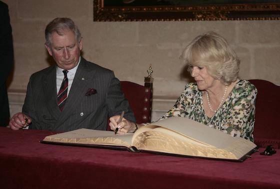 La Duquesa de Cornualles firma en el libro de honor del Ayuntamiento de Sevilla bajo la mirada de su esposo.  Foto: Belén Bargas
