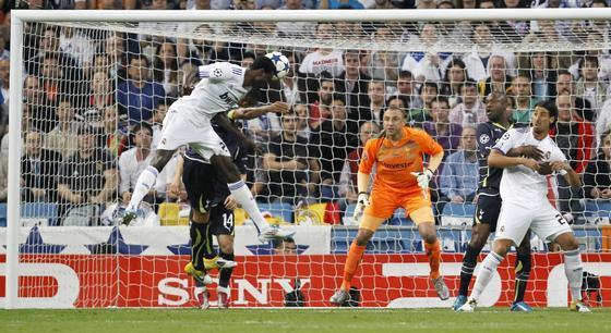 Adebayor remata de cabeza en el primer gol madridista. / AFP
