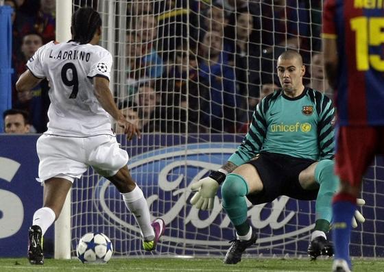 Luis Adriano encara a Víctor Valdés. / Reuters