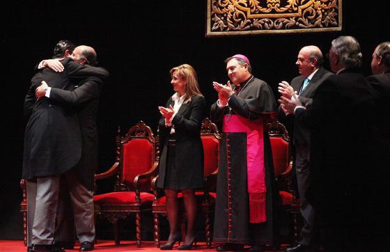 Abrazo entre pregonero y presentador, padre e hijo, al final del acto, junto a la alcaldesa, el obispo y el presidente del Consejo.  Foto: Vanesa Lobo