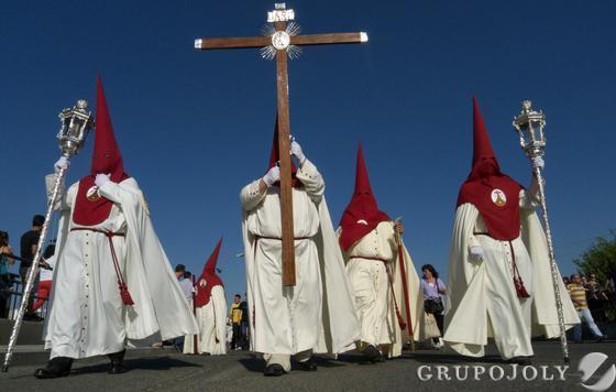 Los nazarenos de la Hermandad de Padre Pío Palmete recorren el barrio.  Foto: Juan Carlos Muñoz