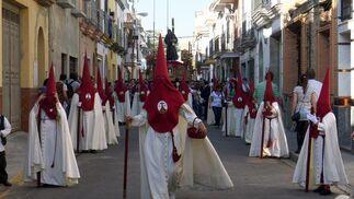 Nazarenos con el paso de misterio detrás por las calle del barrio.  Foto: Juan Carlos Muñoz
